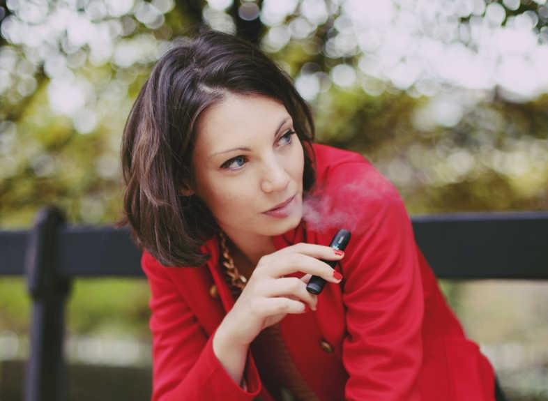 Chica fuma tranquilamente cigarrillo electrónico