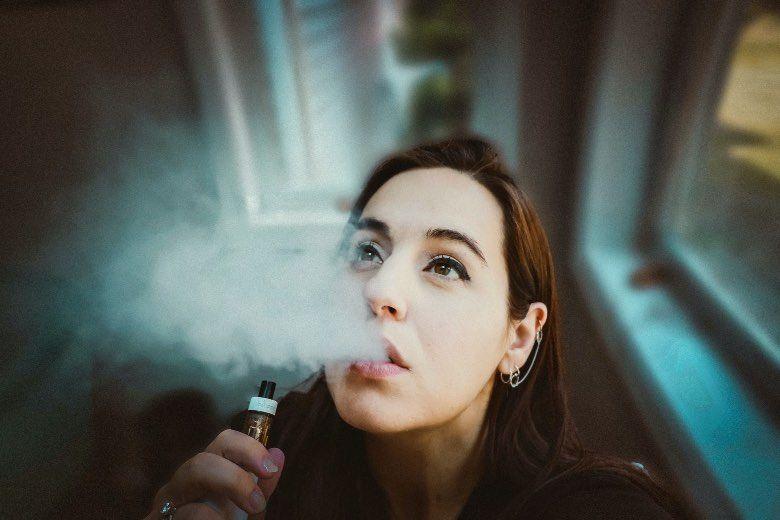 Chica con cigarrillo electrónico para tiro en la mejilla