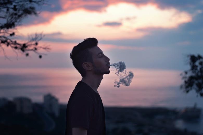 Chico fumando e-cig distante de los niños